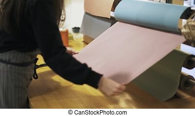 Close up of flower shop assistant cutting paper with scissors
