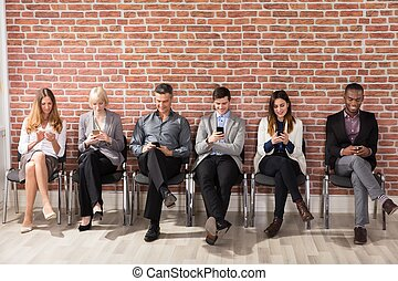 People Waiting For Job Interview Using Cell Phone - Row Of...