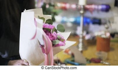 Florist using stapler to attach a pink ribbon to a flower...