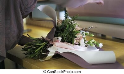 Florist wrapping a bunch of flowers tied by a ribbon on her table