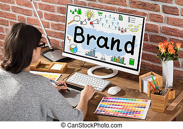 Businesswoman Drawing Brand Chart On Graphic Tablet