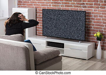 Woman Getting Frustrated With Glitch TV Screen - Rear View...