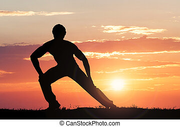 Man Silhouette Doing Exercise At Sunset