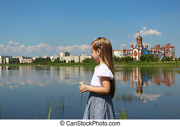 Girl on the background of a lake and a church