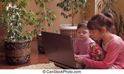 Little sisters with laptop