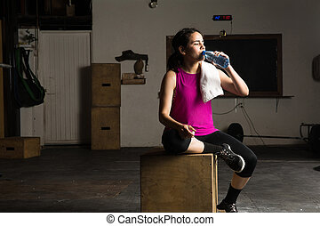 Woman drinking water in a gym