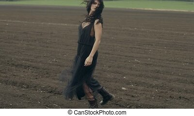 Model in dress and boots posing - Female model wearing light...