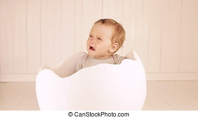 baby cries. A small child is sitting in a toy egg shell.