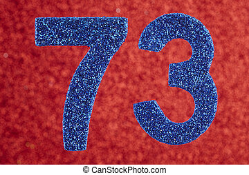 Number seventy-three blue color over a red background....