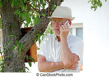 Healthy senior man on the phone outdoor garden