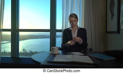 Beautiful blonde young business woman finished her working day, drinking wine and looking at sunset. End workday in the office, hotel room.