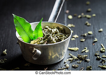 Aromatic green tea in old metal strainer