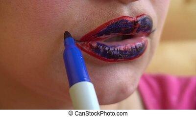 girl paints the red lips blue felt-tip pen.