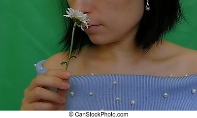 A beautiful, attractive girl inhales the fragrance of a...