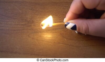 female hand holding a burning match over the table.