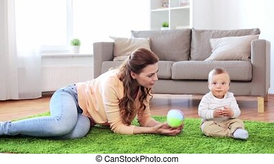 happy mother playing with baby boy at home - family,...
