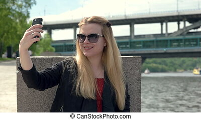 Beautiful young woman with smile doing selfie on a mobile phone