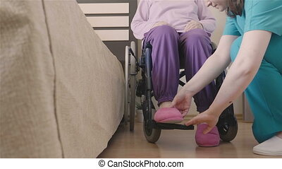 Young nurse caring of elder disabled woman in wheelchair and...