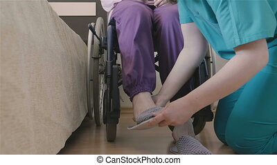 Female caregiver helping senior woman to put her shoes -...