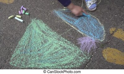 baby hand drawing with colored chalks on the pavement.