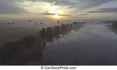 Aerial view of the dawn over the river in the fog.