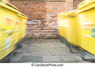 moving yellow dumpster in front of a red brick wall