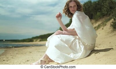 Woman In white dress staying on a beach with flower at the sunny day 4k