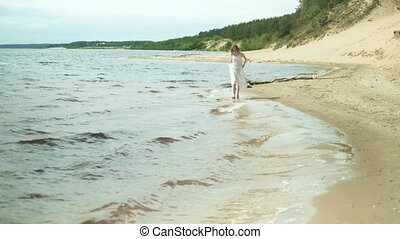 Woman In white dress staying on a beach with flower at the sunny day