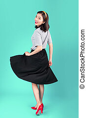 Full body of smiling asian woman dressed in pin-up style dress over blue.