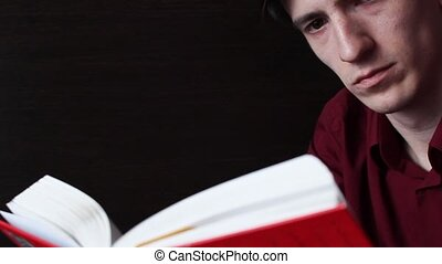 A young guy in a red shirt reading a red book - young guy in...