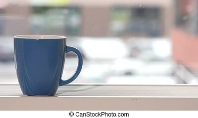 blue cup of hot drink stand on window sill and snowflakes...