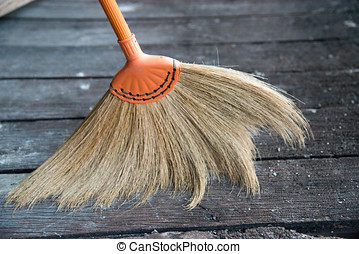 Broom made of grass blossom, sweeping dirt on wooden floor.