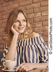 Waist up of woman having cup of coffee