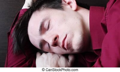 A young guy sleeps at the table in the afternoon, laid his head on his right arm