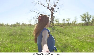 follow me to. Girl holds a man hand go on nature summer....