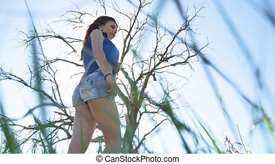 Sexy girl. Girl woman sunlight standing on nature in shorts...