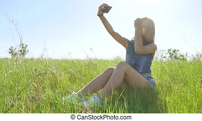 The Selfie girl. Woman doing selfie on smartphone on nature,...