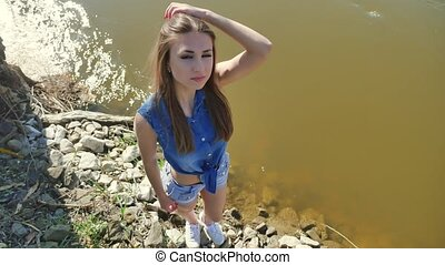 Girl on the river bank. Woman lifestyle stand by the water...