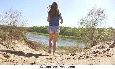 Girl running around in the nature on the sand. woman sport...
