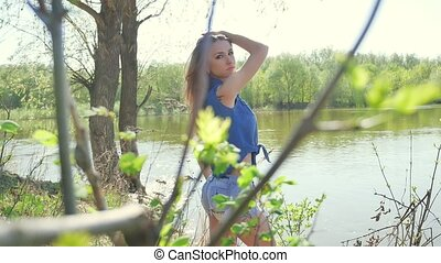 Girl on the river bank. Woman nature lifestyle stand by...