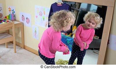 Adorable child unsuccessful try to undress clothes in front of mirror