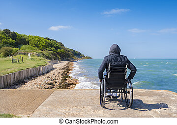 Disabled young man sitting in a wheelchair and looks at the sea
