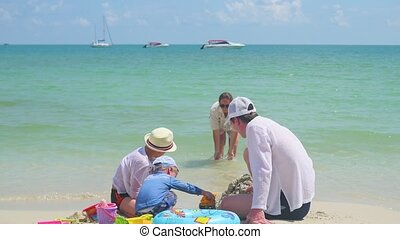 Happy family with children playing on the sandy beach with toys. Tropical island, on a hot day