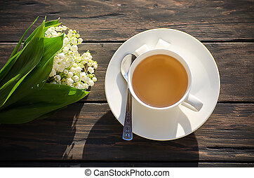 Hot tea in a white cup with a bouquet of flowers on a wooden...