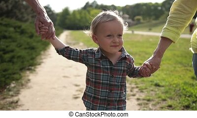 Excited boy walking with grandparents in park - Portrait of...