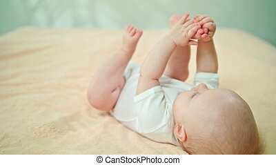 Baby Lying in Bed at Home and Playing with Feet
