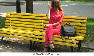 girl on high heels in a red suit with a bag walks in the...