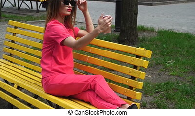 young beautiful lady on high heels in red suit makes selfie...