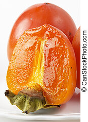 Persimmon slice - Ripe persimmon slice fragment over white...