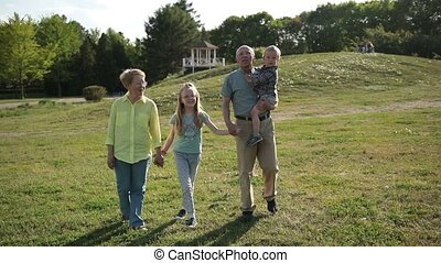 Cheerful family with kids enjoying leisure in park -...